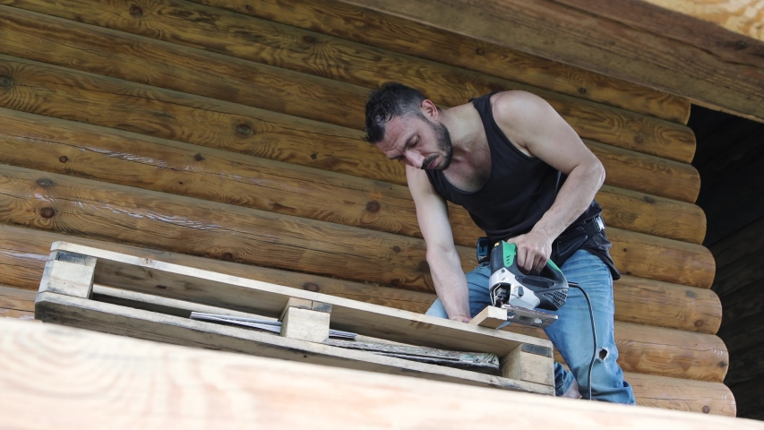 View from below. A young carpenter works with an electric jigsaw. He leaned over the table and holds a wooden piece firmly. UHD. | Shutterstock HD Video #1054277888