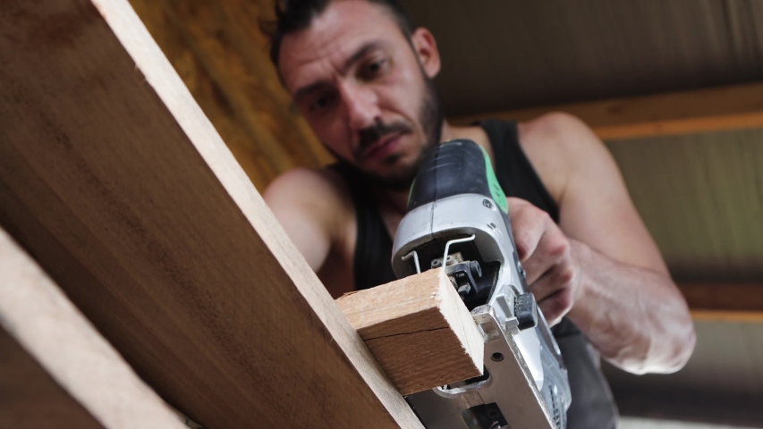 Close up of a young carpenter working with an electric jigsaw. He leaned over the table. Sawdust is flying down. 4K.   Shutterstock HD Video #1054277897