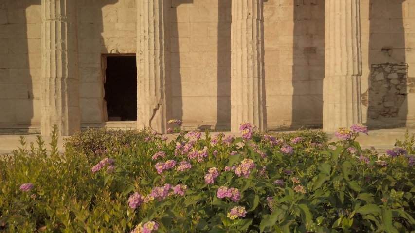 View of the Temple of Hephaestus, the best well-preserved Greek temple, on the ancient Agora of Athens, Greece. Tilt up shot with nautral light and flowers in the foreground. | Shutterstock HD Video #1054278236