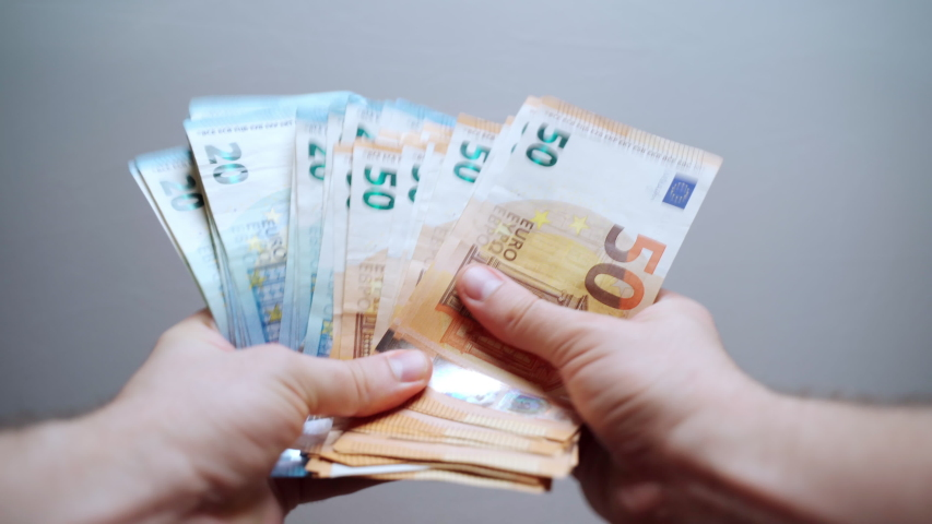 Happy male holding a bundle of euro banknotes and counting money, person won lottery prize in casino, young millionaire calculating his cash award. Finance and success concept   Shutterstock HD Video #1054279403