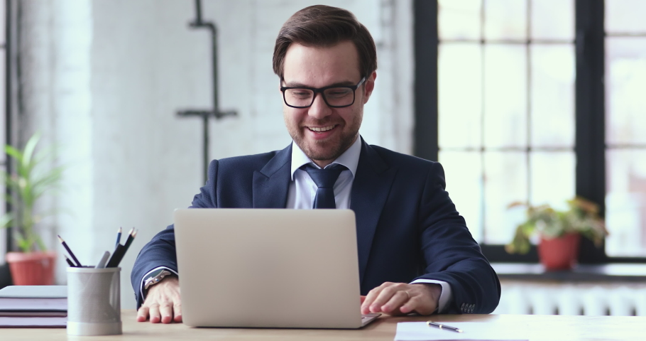 Overjoyed young businessman in formal wear and glasses looking at laptop screen, excited by unbelievable good news. Happy emotional executive celebrating receiving attracted investment notification. Royalty-Free Stock Footage #1054279913