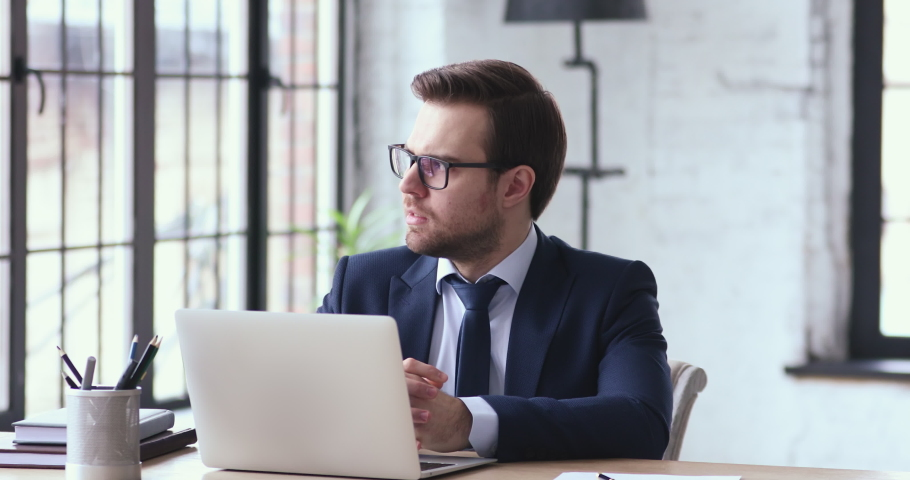 Concentrated young ceo manager employee in suit working on laptop, thinking of hard problem solution. 30s male executive looking at computer screen, doing online financial market research in office. Royalty-Free Stock Footage #1054279916