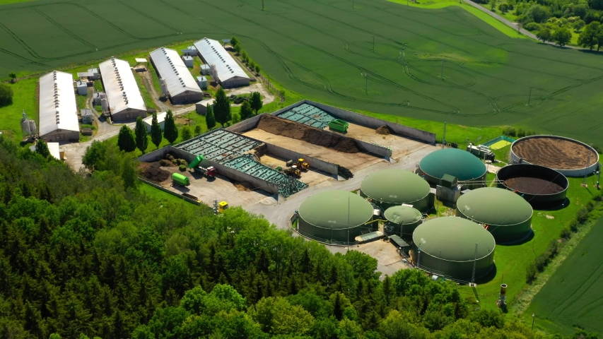 Biogas plant and farm in green fields. Renewable energy from biomass. Aerial view to modern agriculture in Czech Republic and European Union.