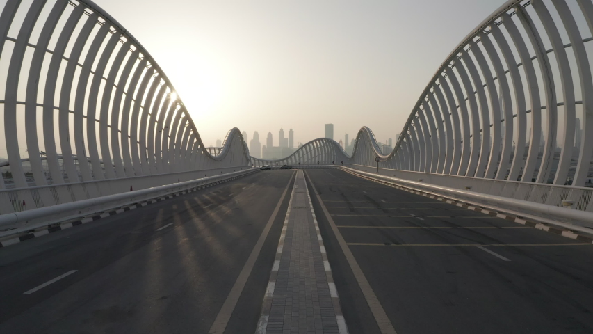 Meydan bridge in Dubai, futuristic bridge during sunset with urban skyline in the background; Modern city architectural roads and bridges concept