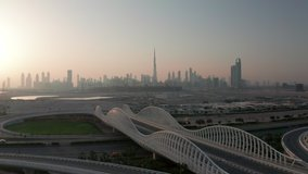 Beautiful aerial view of futuristic Meydan bridge in Dubai with downtown skyline during sunset