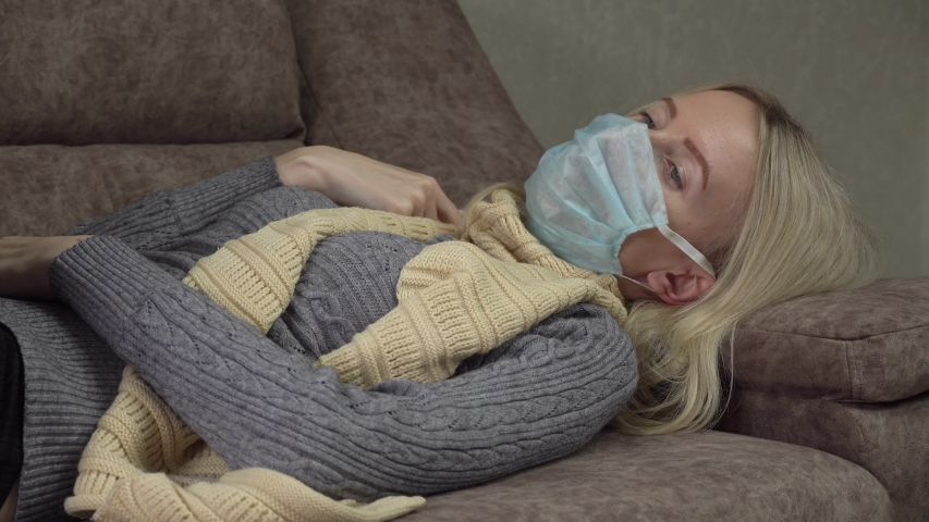 Outbreak of a coronavirus spray from a sore throat. A woman in a mask treats her throat with a spray, lies on the bed coughing, spray in her mouth. Home treatment, apartment in the room. cough | Shutterstock HD Video #1054281116