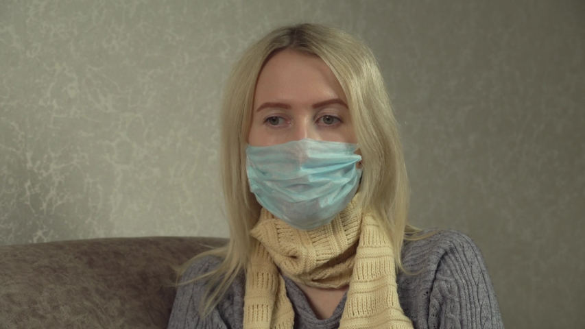 Outbreak of a coronavirus spray from a sore throat. a masked woman who treats a throat with a spray and sprays in her mouth. Home treatment, apartment in the room. | Shutterstock HD Video #1054281122