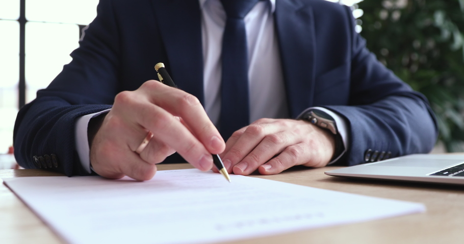 Close up concentrated young businessman in formal wear carefully reading contract terms of conditions, putting signature on paper. Focused executive ceo signing report after checking information. | Shutterstock HD Video #1054282325