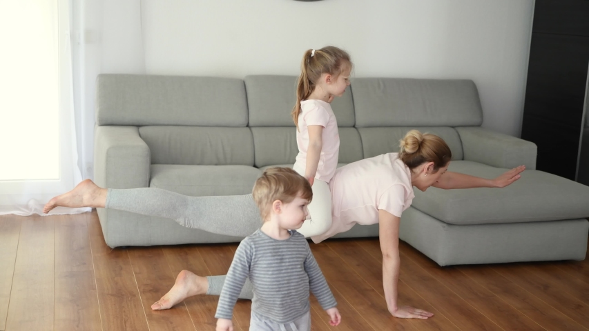 Mother and daughter doing gymnastics at home. | Shutterstock HD Video #1054283312