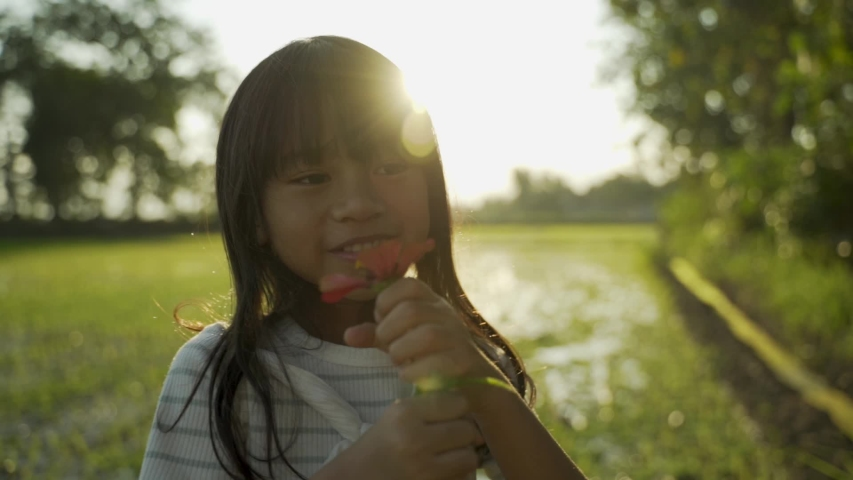 Lovely asian daugther giving flower to her mother while playing in the field