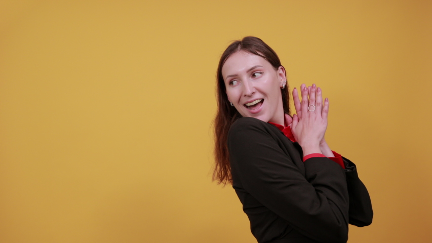 Young Attractive Brunette Woman In Black Stylish Suit, Red Shirt On Yellow Background, Happy Female Smile Shows Direction Thumb Fingers.  Royalty-Free Stock Footage #1054284089