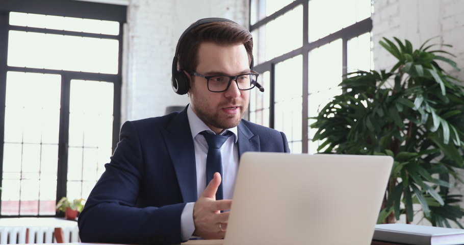 Smart male company leader in suit waring headset with mic, holding negotiations talk online with employees, using corporate software in office. Professional lawyer consulting clients by video call.