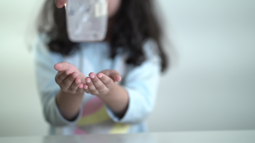 A girl cleaning hands With Sanitizer to protect herself healthy. Clean hands keep us from spreading viruses like COVID-19.Effective way to keep yourself healthy. Royalty-Free Stock Footage #1054284965