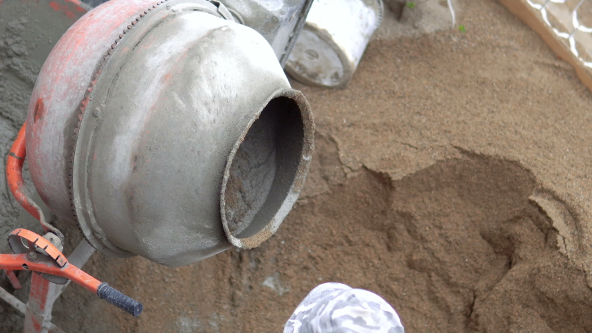 Old dirty concrete-mixer near sand heap at small construction site. Small portable cement mixing machine at home. Building site | Shutterstock HD Video #1054285445