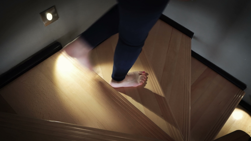 A barefoot female walking down over a wooden stairs lit by led lights at night in luxury home