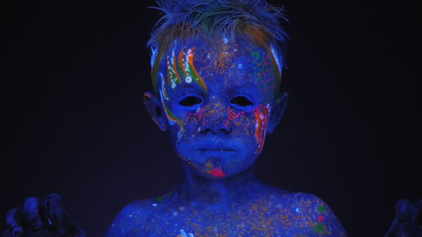 A close-up of a small boy's face with ultraviolet drawings on his body and face, he raises his hands and growls. A small child is painted with fluorescent paint.