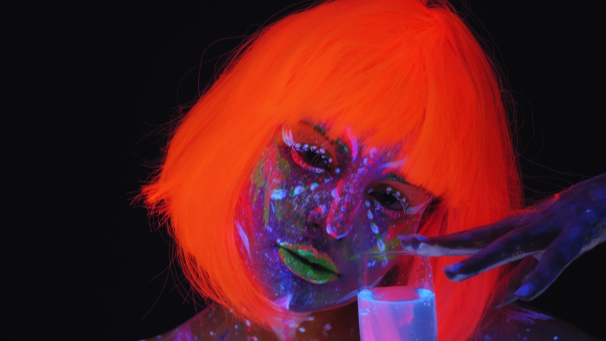 A sexy girl with a UV pattern on her body and an orange wig holding a glass of champagne that glows in the light of fluorescent lamps. Halloween party. Body art glowing in UV light. | Shutterstock HD Video #1054289339