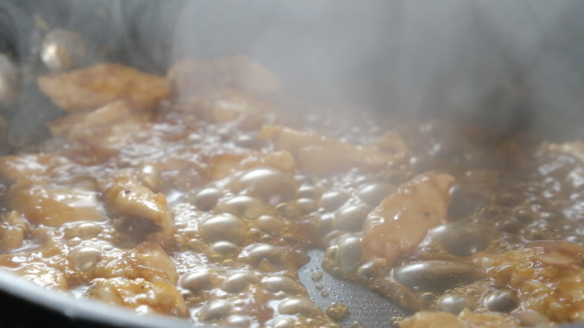 Slow motion frying chicken meet in pan with dark soy sauce with steam rising from pan. Close up Cooking chicken in Sauce.