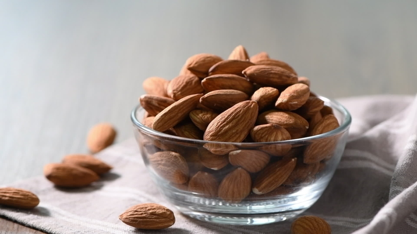 Sprinkle salt on almonds nut. product rich in minerals and vitamins. Almond turns in a shot. Almond kernels rotating. slow motion and side view. | Shutterstock HD Video #1054290293