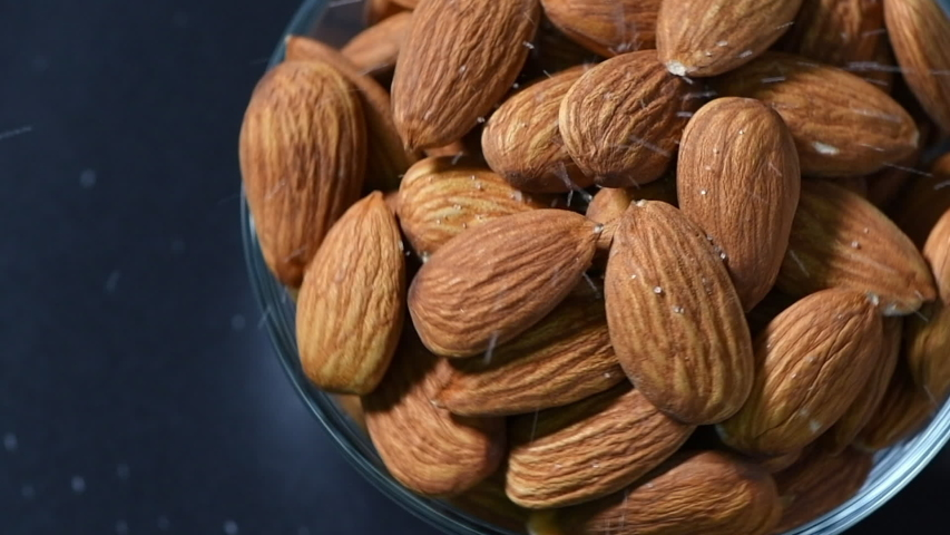 Sprinkle salt on almonds nut. product rich in minerals and vitamins. Almond turns in a shot. Almond kernels rotating. slow motion and top view. | Shutterstock HD Video #1054290296