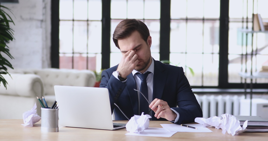 Stressed overwhelmed young businessman in suit working on computer, suffering from eyes fatigue or having painful feelings. Exhausted executive manager overworked in office, burnout concept.
