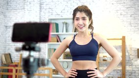 20s young Asian woman in sportswear doing talking to camera and explaining fitness tutorials online. Healthy girl blogger in living room at home. Teaching online bodybuilding class concept.