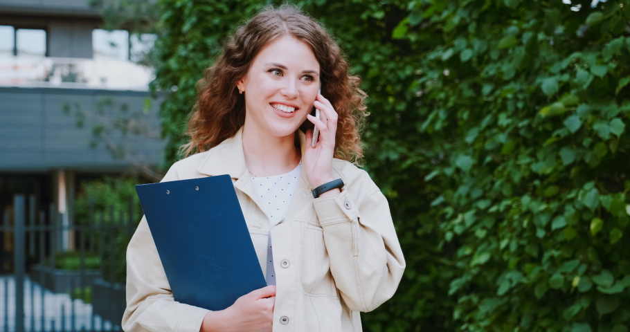 Young woman talks by phone, real estate agent or office worker outdoors. Having a business call, freelancer girl. She carries a pad for papers, documents folder. Pretty confident manager. | Shutterstock HD Video #1054292678
