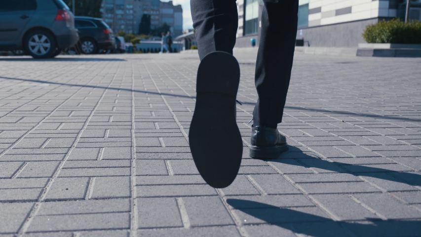 Rear back view feet of businessman commuting to work. Confident guy in leather shoes and suit being on his way to office building Royalty-Free Stock Footage #1054293320