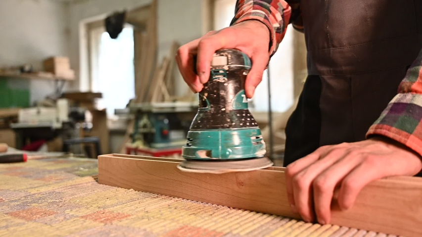 Working process in the carpentry workshop.A man Using Electric Sander for wood in a carpentry workshop.Profession, carpentry, woodwork and people concept | Shutterstock HD Video #1054293536