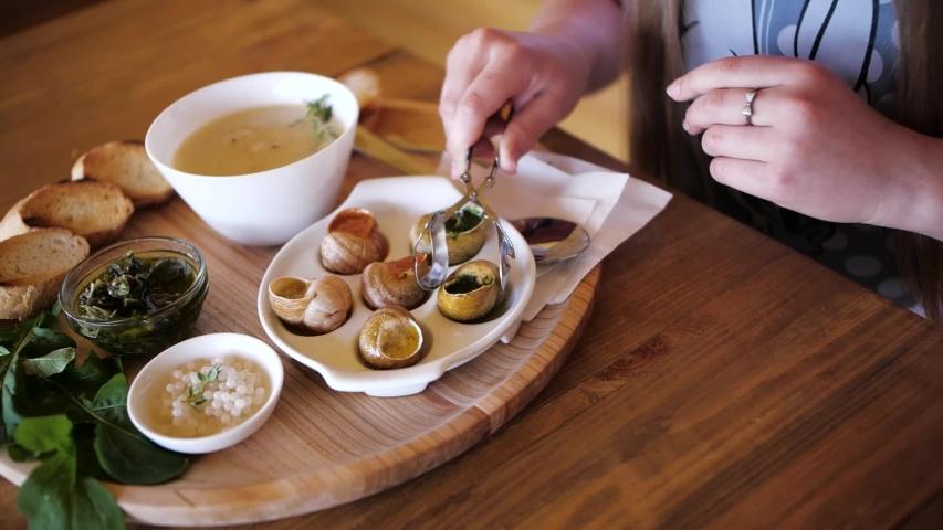 The girl eats snails. Delicacy | Shutterstock HD Video #1054294556