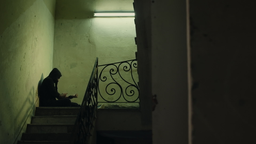 Social issues and drugs, young man injecting heroin with syringe and sitting on stairs of abandoned house. Junkie with addiction, substance abuse, drug addict