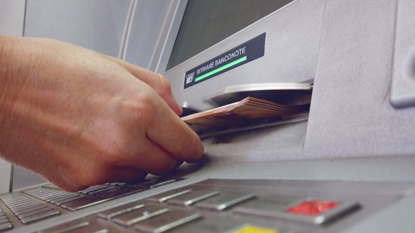 "ATM machine hand taking cash bank withdrawal service with the italian text ""ritirare banconote"" meaning take cash 