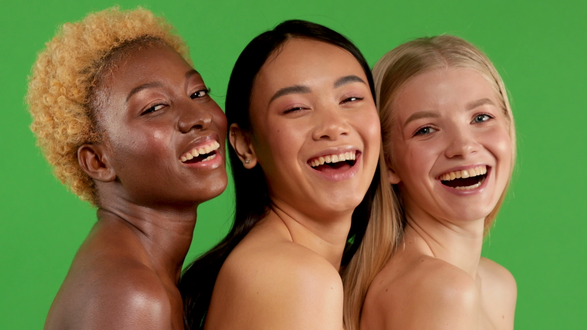 Beautiful Girls White European,Asian and Black African American Beautiful Sexy young womens with Natural Healthy Skin Smiling isolated green background. Racial equality