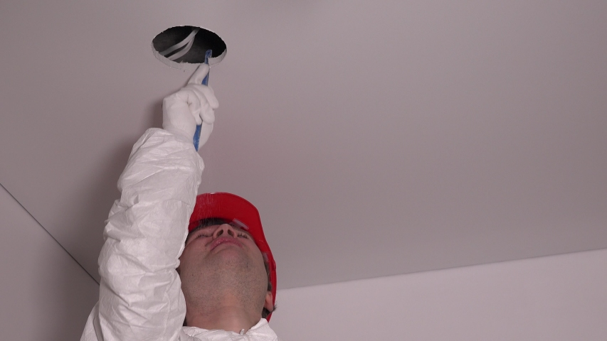 Close up of professional man worker make hole in the ceiling for lighting LED lamps. 4K | Shutterstock HD Video #1054296191