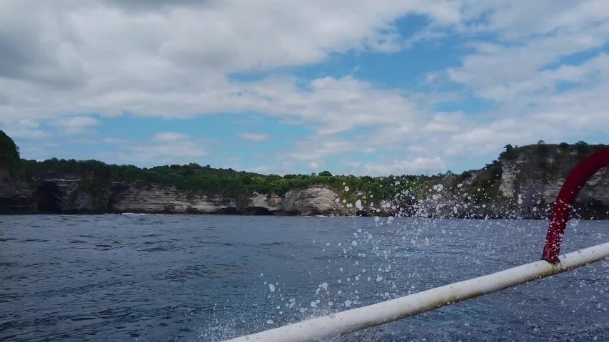A motor boat is sailing along beautiful cliffs, a motor boat is sailing along the waves along cliffs   Shutterstock HD Video #1054296389