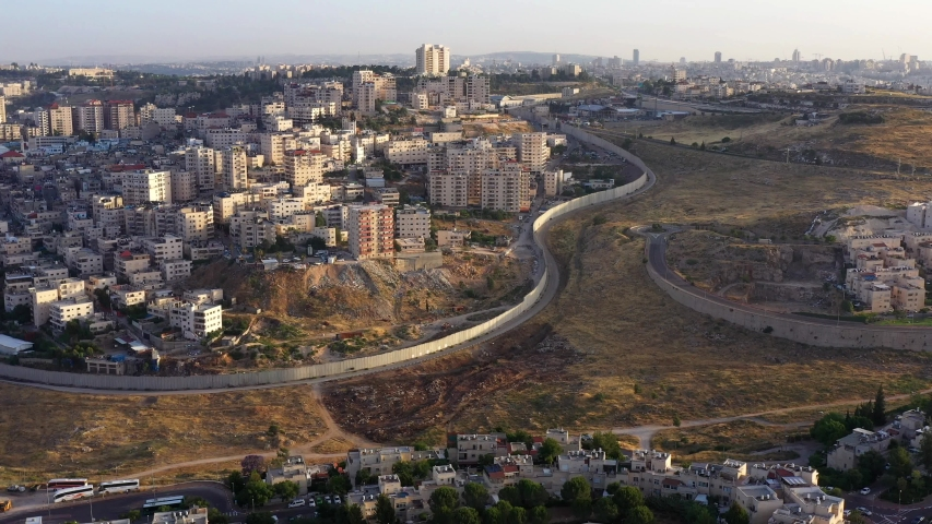 Security Wall divide Israel and Palestine. Panorama Aerial view Drone View over Anata Refugee Camp And Jewish Pisgat Zeev neighborhood.  | Shutterstock HD Video #1054297718