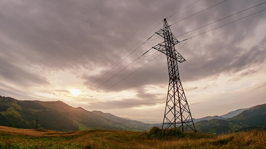 Wide view of clouds passing behind power line pylon in sunset sky background, time lapse | Shutterstock HD Video #1054297811