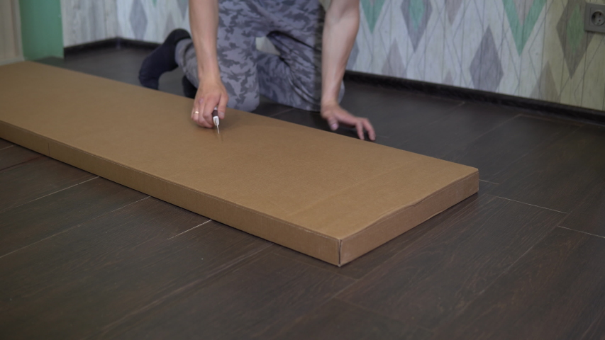A man opens a new box with accessories for assembling a cabinet with a knife