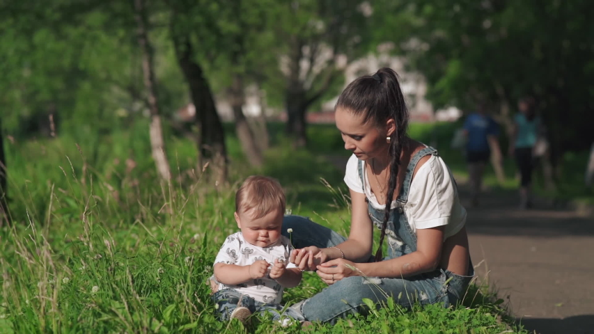Pretty tender mommy and her little son sitting on the grass in the picturesque park . Beautiful young mother giving a small flower to her cute child. Concept of motherhood, love happiness and beauty.