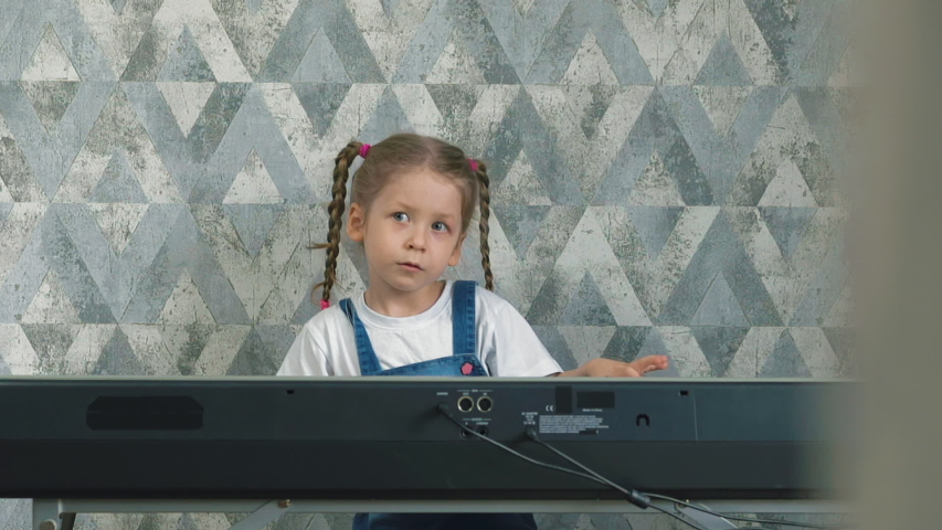slow motion little girl with long pigtails plays on electronic piano at home, in self-isolation and quarantine mode, sad ballad