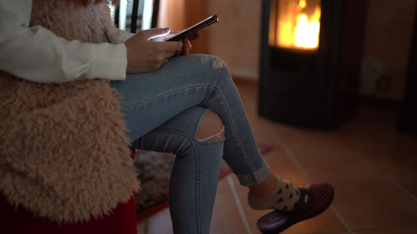 Browsing online concept, modern technologies and cellphone. Fashion girl sitting at home on armchair, shaking legs and using smartphone. Woman on background of burning fire in pellet stove | Shutterstock HD Video #1054302281