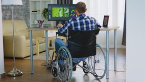 Disabled filmmmaker in wheelchair working on post production of a new video. Handicapped invalid paralysed freelancer, immobilized entrepreneur working from home, ilness and disability