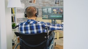 Video editor in wheelchair working on film post production. Handicapped invalid paralysed freelancer, immobilized entrepreneur working from home, ilness and disability