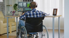 Disabled video editor sitting on wheelchair doing post production on film. Handicapped invalid paralysed freelancer, immobilized entrepreneur working from home, ilness and disability