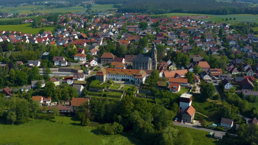 Aerial view of the city and monastery Neudrossenfeld in Germany on a sunny day in spring. During the coronavirus lockdown. | Shutterstock HD Video #1054303172