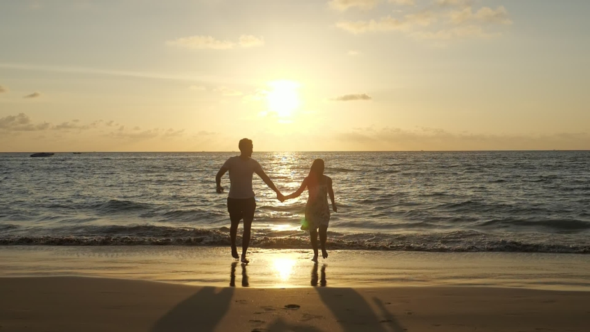 Silhouettes of joyful couple running along beach joining hands against ocean waves at tropical sunset slow motion