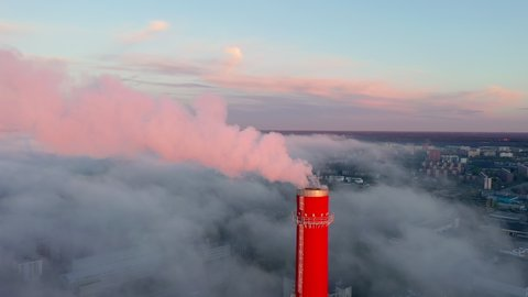 The tip of the tall red chimney tower in Tallinn Estonia with the smoke coming out from the boiler house.geology shot