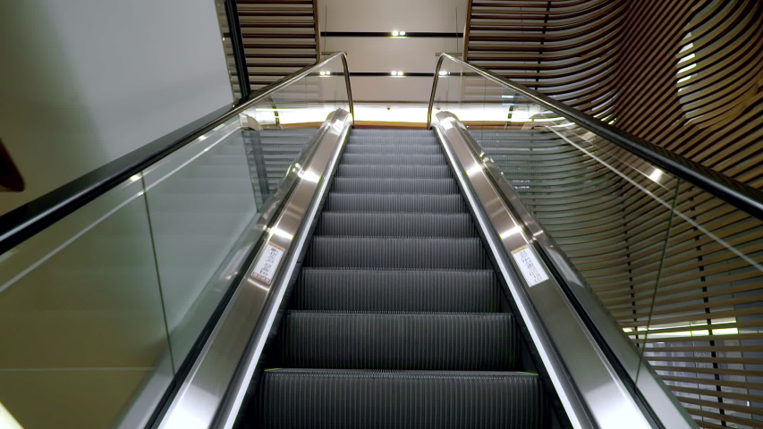 Moving up the escalator with glass sides and metal steps Royalty-Free Stock Footage #1054304411