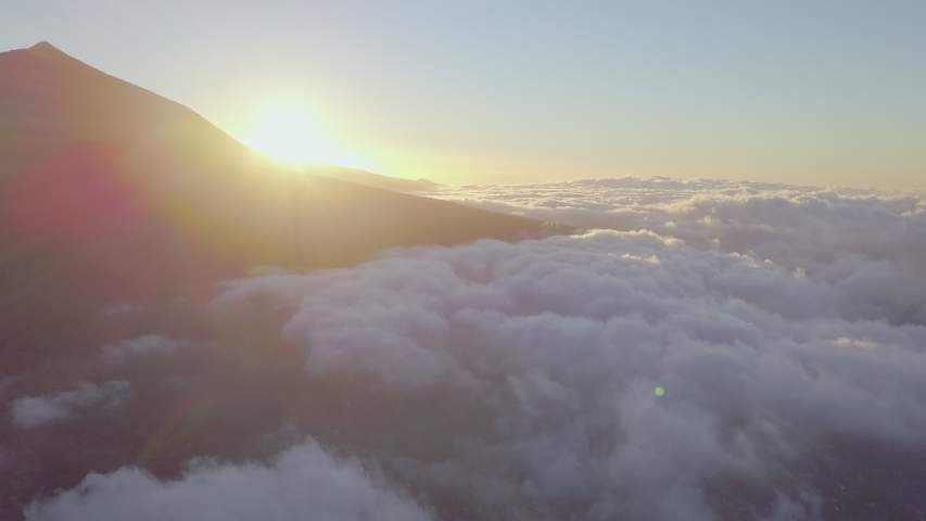 The sun and the thick sea of clouds in the sky in Tenerife Spain with the view of the volcano El Teide .geology shot