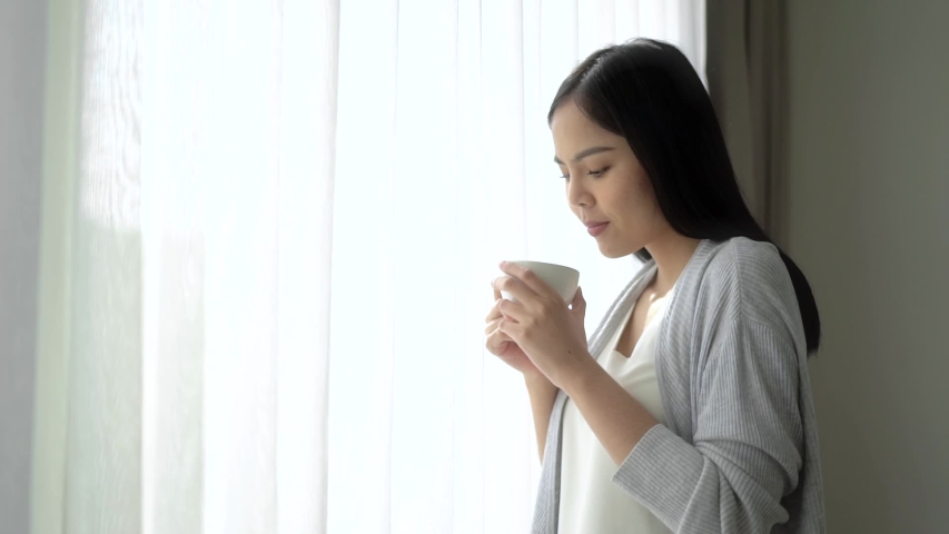 Young asian woman opening curtains looking out window enjoying fresh new day feeling rested and drinking coffee at home. Slow Motion Full Hd. Royalty-Free Stock Footage #1054307189